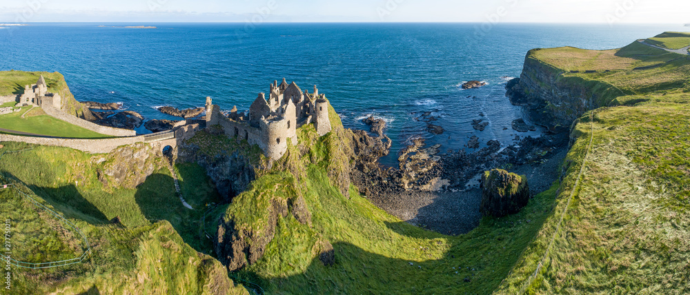Fototapety, obrazy: Ruins of medieval Dunluce Castle on a steep cliff. Northern coast of County Antrim, Northern Ireland, UK. Aerial wide panorama in sunrise light