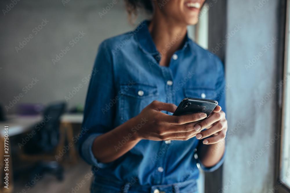 Obraz Businesswoman with mobile phone in hand fototapeta, plakat