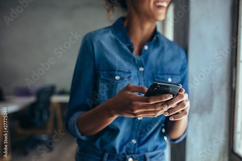 Obraz Businesswoman with mobile phone in hand - fototapety do salonu
