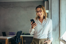 Smiling Businesswoman Using Phone In Office