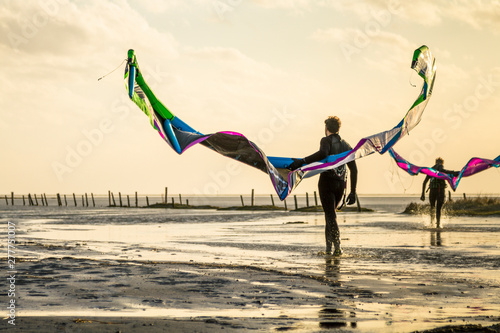 Kiteboarders with their kites during sunset at the coast of the German Sea in St. Peter Ording, Germany.