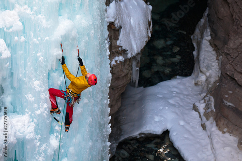 Alpine climber climbing the 45 meter/148-foot Tokumm Pole above the Tokumm Creek in the scenic Marble Canyon, BC in Kootenay National Park near Banff, Alberta. The rugged, narrow slot canyon is a popular summer destination with the turquoise waters of Tokumm Creek flowing at the bottom. But in the winter it is a hotspot for ice climbing, snowshoeing, and nordic skiing.