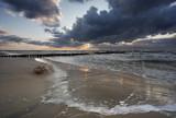 Morze zachód słońca - falochron z chmurami i sztormem