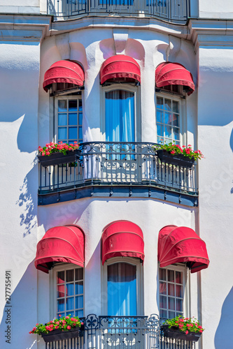 Photo Red colorful blinders at the white ornamented hotel Diplomat with french balcony