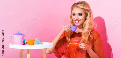 panoramic shot of beautiful smiling girl with toy cup on pink, doll concept