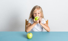 Beautiful Blond Girl Eating A Green Apple Sitting At The Table