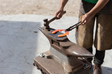 Unrecognisable Farrier Holding Red Hot Horseshoe On An Anvil