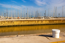 Misa River Channel At The Port Of Senigallia, Province Of Ancona, Marche, Italy With A White Painted Mooring Bollard