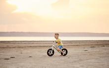 Little Boy Riding Bike At Suns...