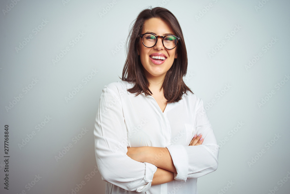 Fototapeta Young beautiful business woman wearing glasses over isolated background happy face smiling with crossed arms looking at the camera. Positive person.