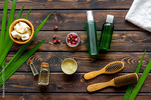 Cosmetics for hair care with jojoba, argan or coconut oil in bottle on wooden ba Canvas-taulu