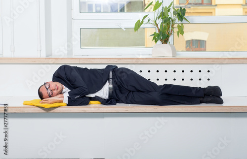 Young business man sleeping in the office. Tired at work.