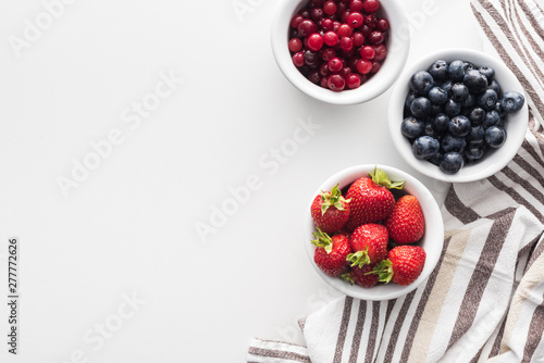 top view of sweet cranberries and blueberries, strawberries on bowls