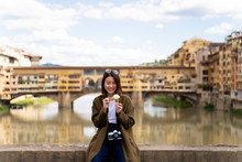 Italy, Florence, Young Tourist Woman Eating An Ice Cream Cone At  Ponte Vecchio