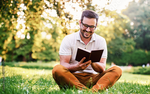 Foto  Man reading a book in the park. Education, lifestyle concept