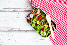 Lunchbox With Green Salad, Green Asparagus, Strawberries And Daisies