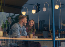 Two Friends Talking In A Cafe. Shot Through Window.