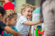 Happy boy with other children and pre-school teacher in kindergarten