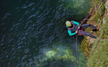 Cenital View Of A Man Wearing A Neoprene Sit And Yellow Helmet Descending With Strings Of Rappel A Vertical Cliff Of Rocks And Plants To Go To The Water Of River To Canyoning In A Day Of Summer