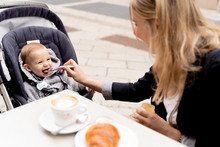 Mother Feeding Laughing Baby Boy In Stroller