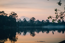 Landscape Of Tranquil Lake Water With Haze Above In Sunrise Hours, Thailand
