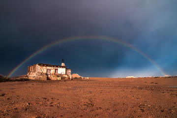Lonely house in desert and rainbow in sky