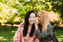 Young Caucasian Woman Smiling And Whispering Secret Into Ear Of Smiling Asian Friend While Spending Time In Park Together