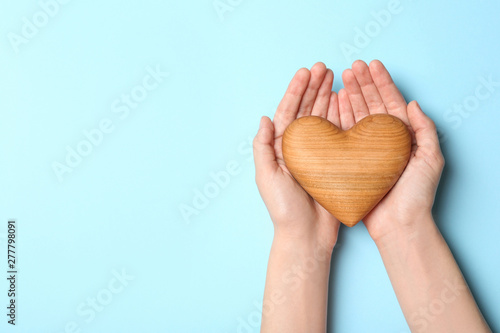 Photo Woman holding heart on blue background, top view with space for text