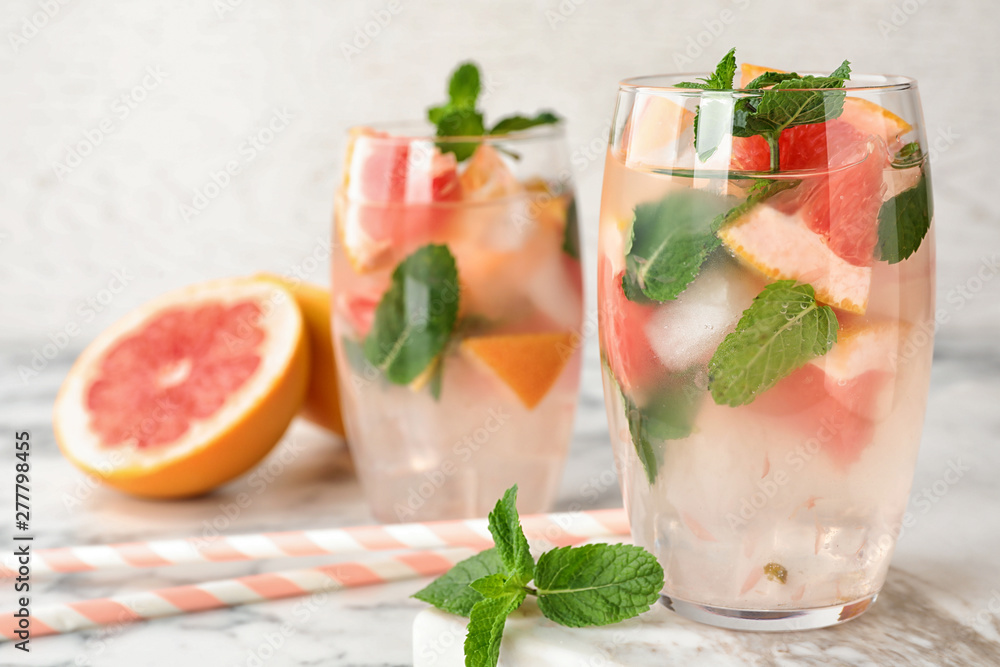 Fototapety, obrazy: Glasses of refreshing drink with grapefruit and mint on marble table, space for text