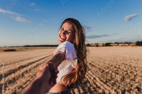 Follow me. Young woman holding hand and leading man to the beautiful nature sunset yellow landscape. View from back side, POV. Romantic couple travel, spend summer vacation together outdoors.