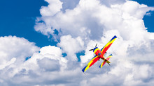 An Acrobatic Plane, Flying In The Blue Sky With White Clouds, Doing Acrobatics