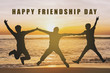 "Three Silhouette people jumping for joy on sunset beach with ""happy friendship day"" text"