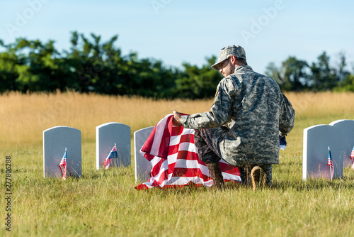 man in military uniform and cap holding american flag while sitting in graveyard Fototapeta