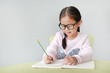 Smiling little Asian child girl wearing eyeglasses and write in a book or notebook with pencil sitting on kid chair and table against white background.