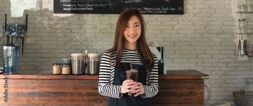 Woman coffee shop owner serving ice americano, young entrepreneur, dimenstion image for banner - 277818600