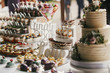Delicious candy bar at wedding reception. White and chocolate desserts with fruits, macarons, cake, cupcakes on stand, modern sweet table at wedding or baby shower. Luxury catering concept