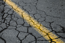 Cracked Asphalt Road With Yell...