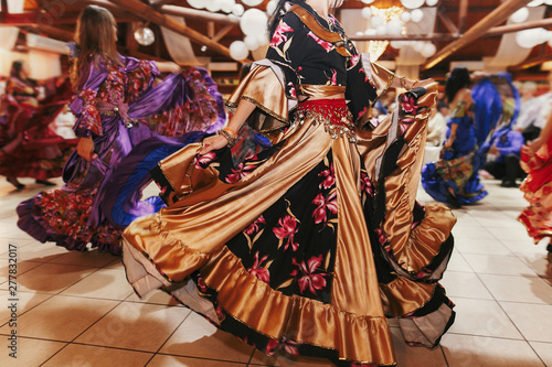 Photo  Beautiful gypsy girls dancing in traditional gold floral dress at wedding reception in restaurant