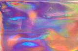 Fototapeta Tęcza - Holographic abstract colorful backdrop. Abstract face. Holographic color wrinkled foil. Iridescent art. Trendy creative gradient. Blurred background.