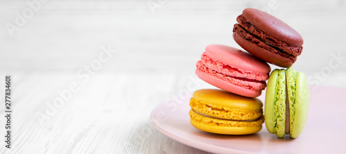 Poster Macarons Sweet and colorful macarons on a pink plate over white wooden background, side view. Copy space.