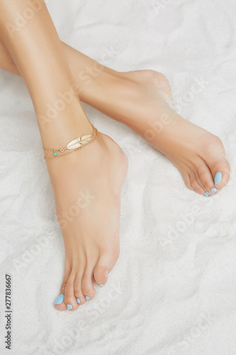 Cropped front shot of lady's legs with blue pedicure, wearing two-row ankle bracelet, adorned with golden insert in view of feather and turquoise bead Canvas Print