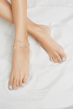 Cropped Front Shot Of Lady's Legs With Blue Pedicure, Wearing Cascade Ankle Bracelet, Adorned With Silver Pendants In View Of Leafs And Massive Bead. The Girl Is Crossing Legs On White Background.