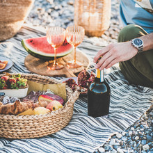 Summer Beach Picnic At Sunset. Young Couple Sitting On Blanket Having Weekend Picnic Outdoor At Seaside With Fresh Seasonal Fruit, Tray Of Tasty Appetizers And Bottle Of Sparkling Wine, Square Crop