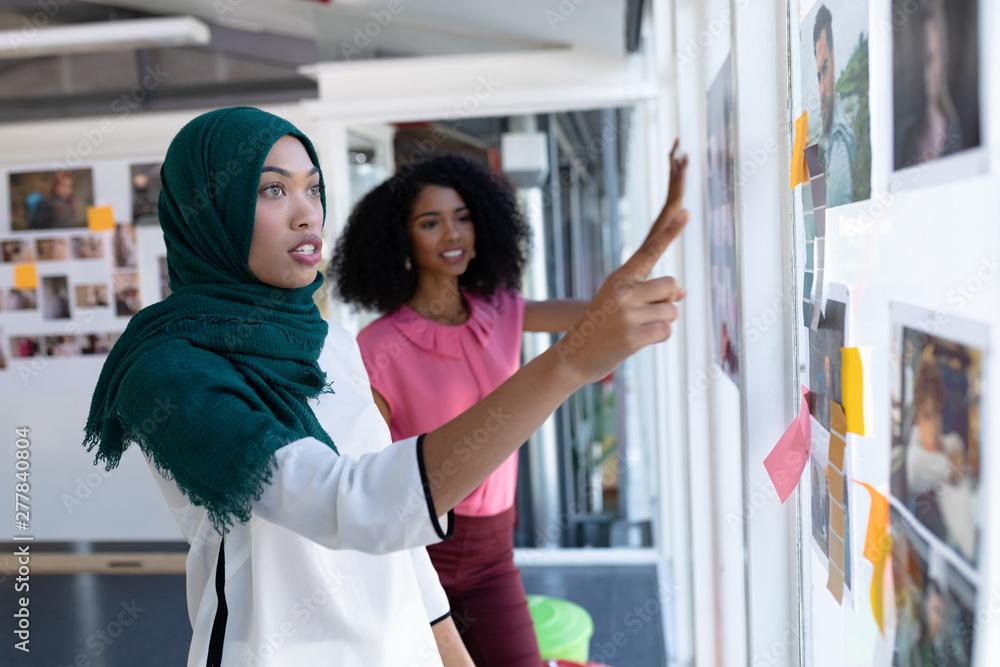 Fototapeta Female graphic designers discussing over photographs in office