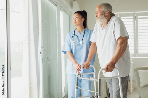 Healthcare worker with man using walking support Canvas Print