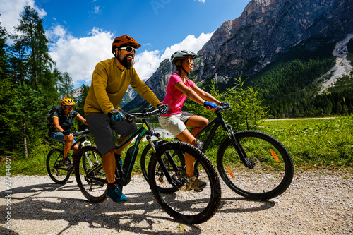 Tourist cycling in Cortina d'Ampezzo, stunning rocky mountains on the background Fotobehang
