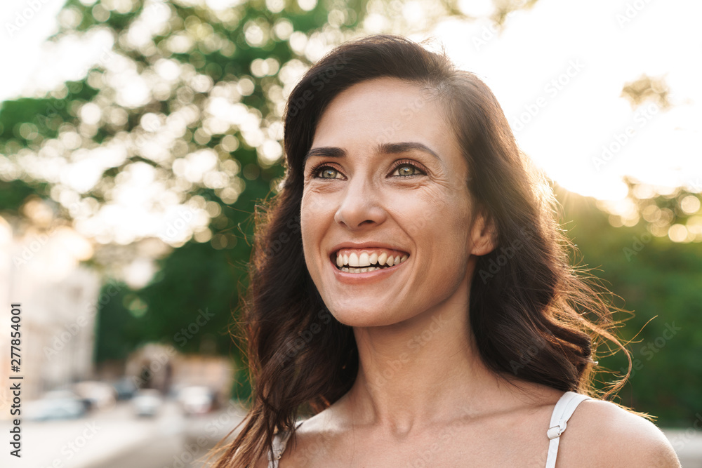 Fototapety, obrazy: Portrait of charming brunette woman smiling while walking through city street