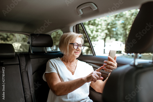 Senior business woman talking with phone while sitting on the back seat in the modern car. Concept of a business life on retirement - 277854472