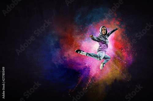 Poster Dance School Modern female dancer jumping in hoodie with colourful splashes background. Mixed media