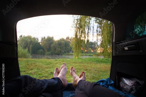 Fotografía  Man and woman relaxing in the trunk of a car near a lake